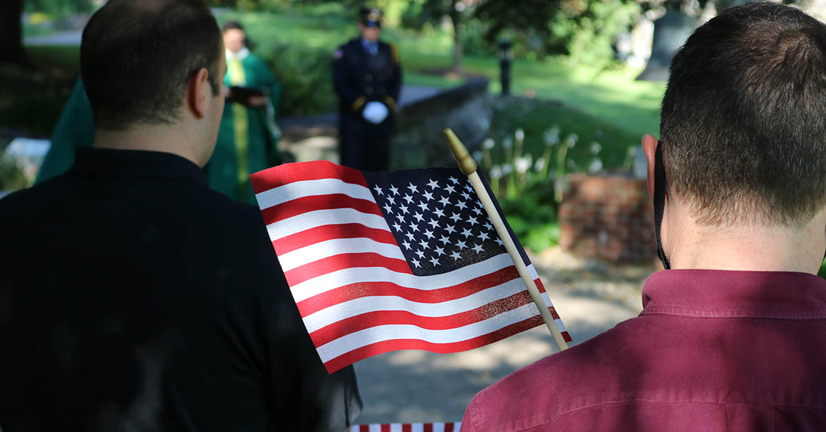 person holding american flag during sept 11 prayer service at saint vincent college